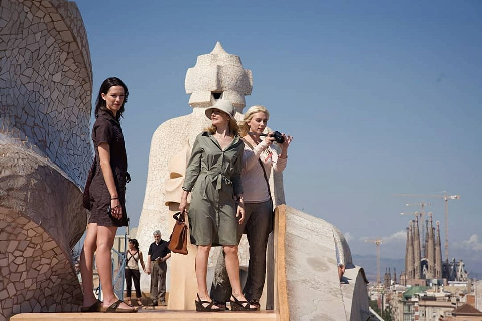 3 women photographing the roof of La Pedrera with the Sagrada Familia in the background