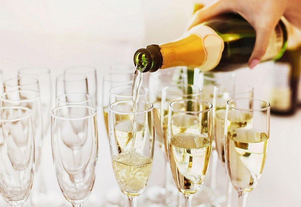 Person pouring cava into glasses