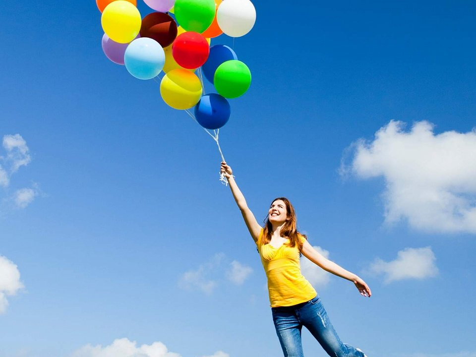 Woman holding onto balloons flying in the sky