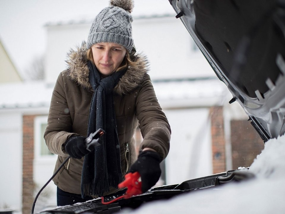Woman in winter clothing trying to jumpstart her car in the cold.