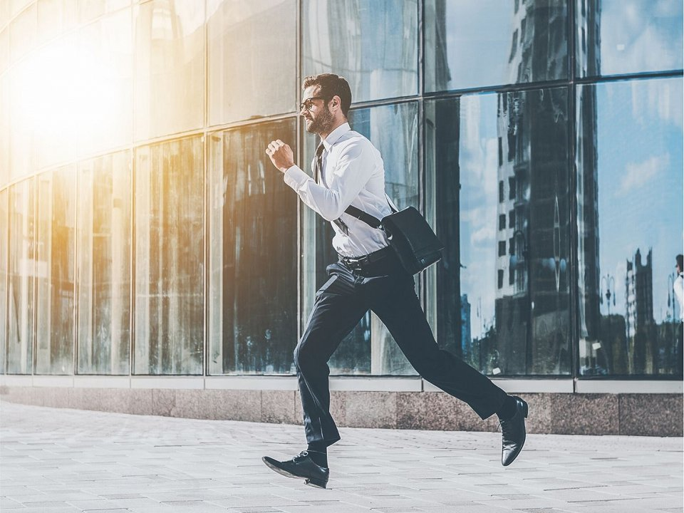 Man is running in front of a glass building.