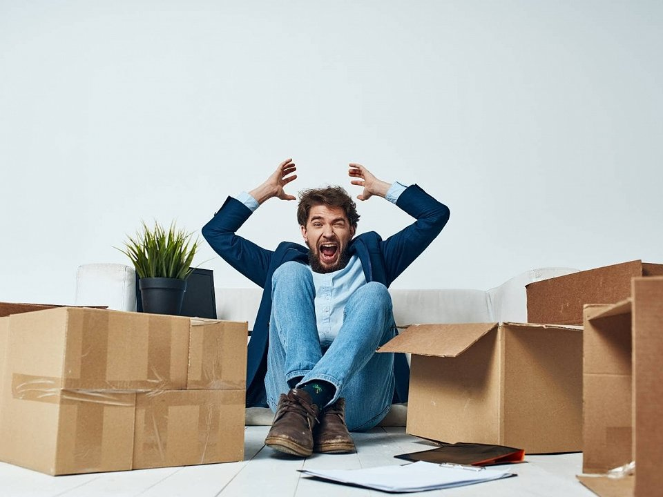 man with hands up in despair surrounded by cardboard boxes