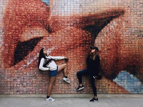 two girls posing in front of street art mural