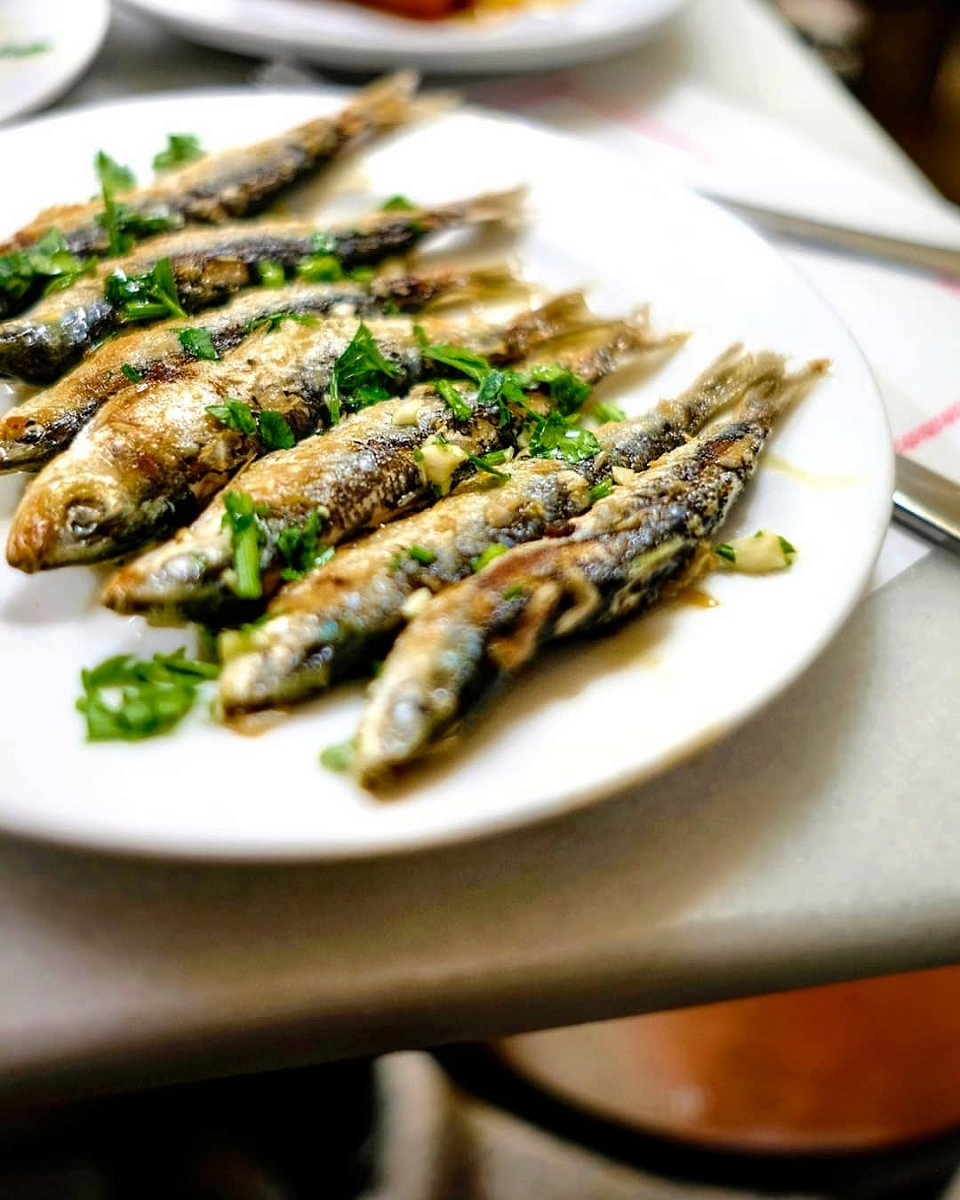 Freshly fried sardines on a plate, sprinkled with parsley