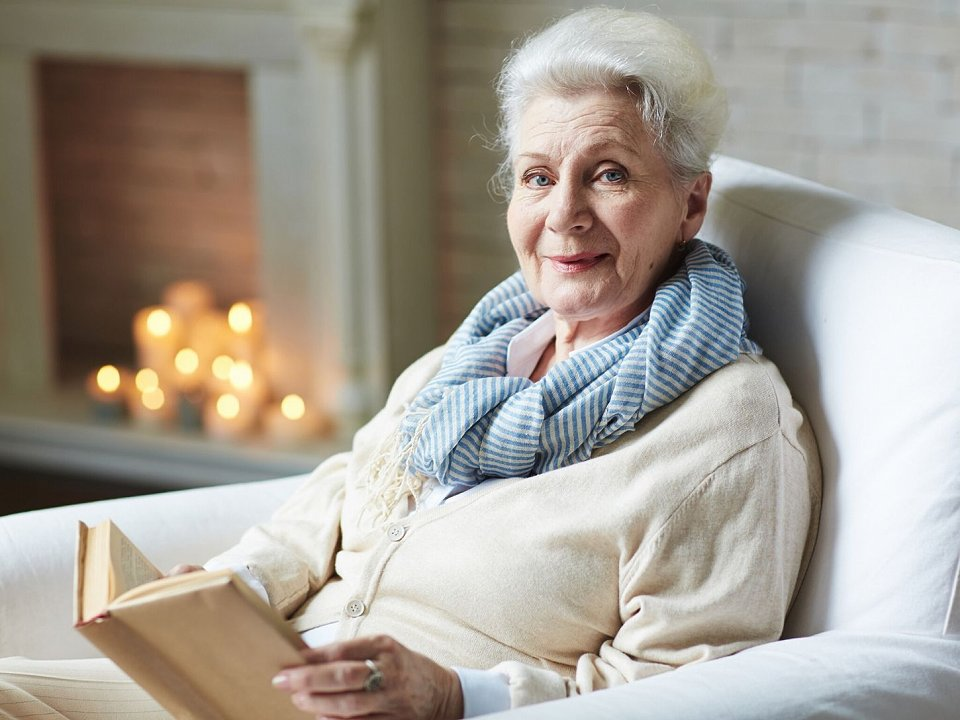 White-haired woman sitting in front of the fireplace with a book.