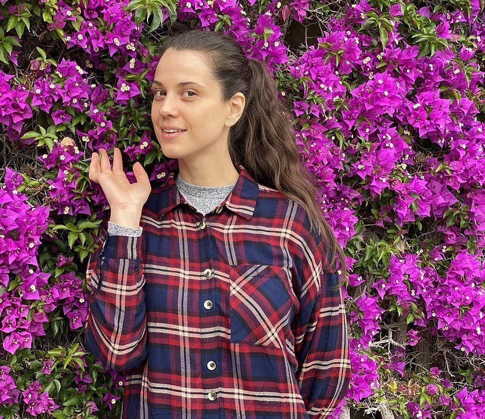 student in front of beautiful pink flowers