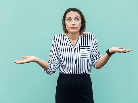 Woman looking confused with hands up at her sides
