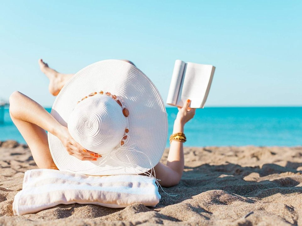 Woman with sun hat lying on the beach, reading a book