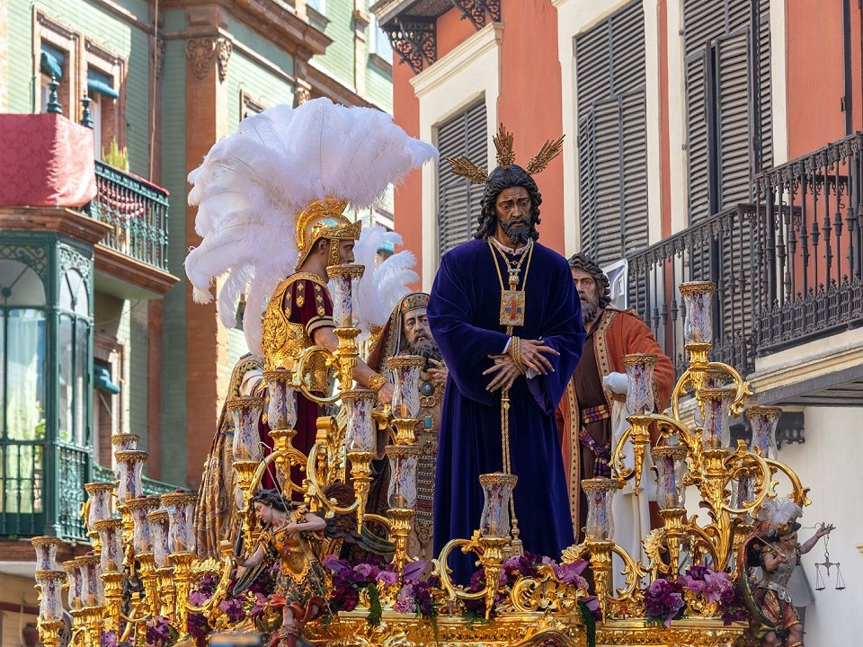 Jesus on an Easter float with Spanish buildings in background