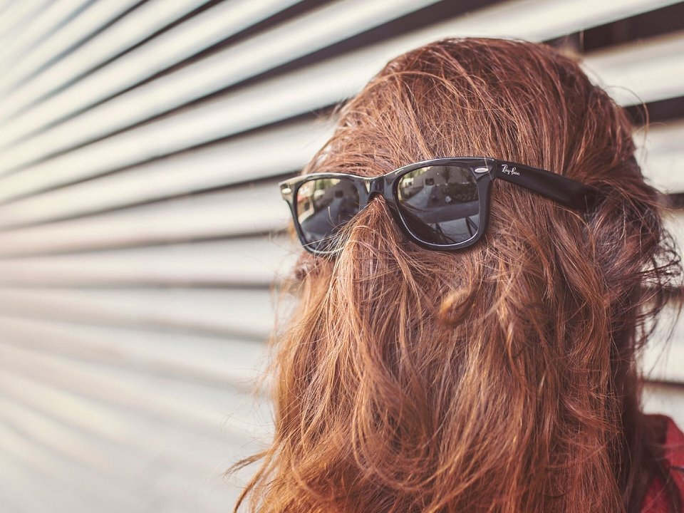 Person with long hair covering face and sunglasses over it