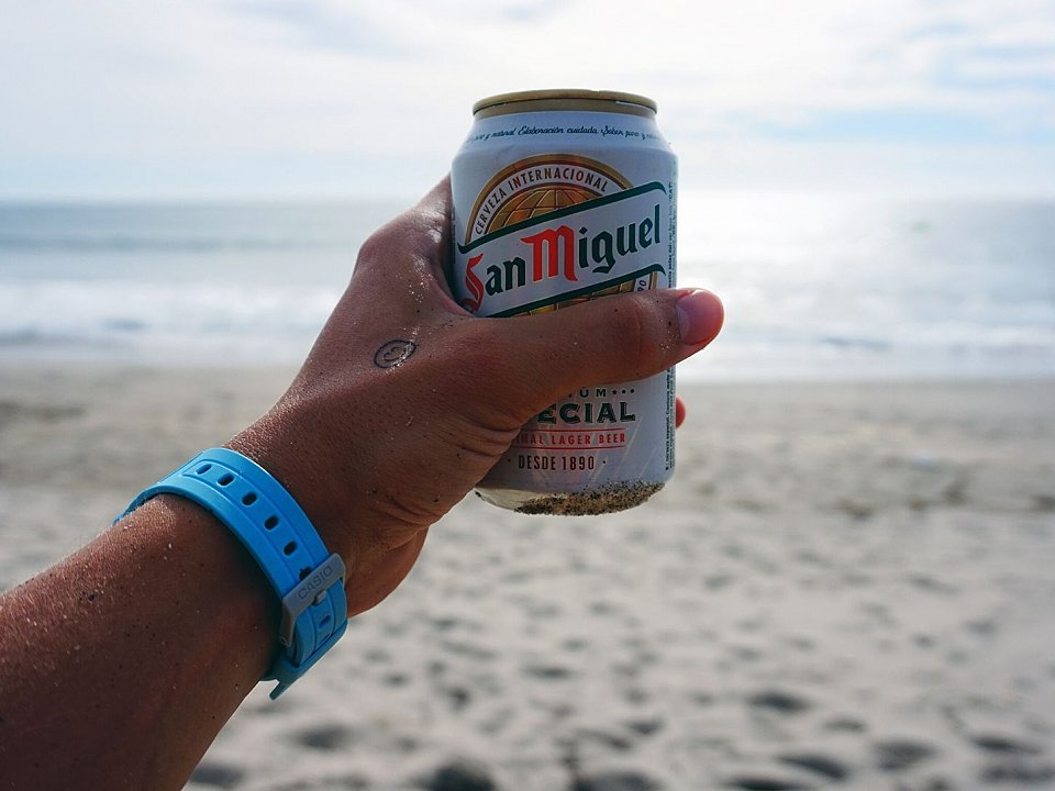 Hand holding can of San Miguel beer in front of the beach