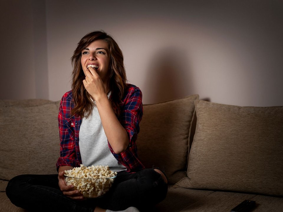 Girl sitting on couch eating popcorn in front of TV