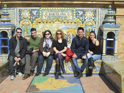 Group of friends in Plaza de España in Sevilla sitting on the Barcelona bench