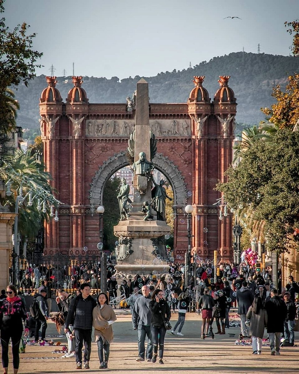 Many people walking along the passage in front of the Arc de Triomf