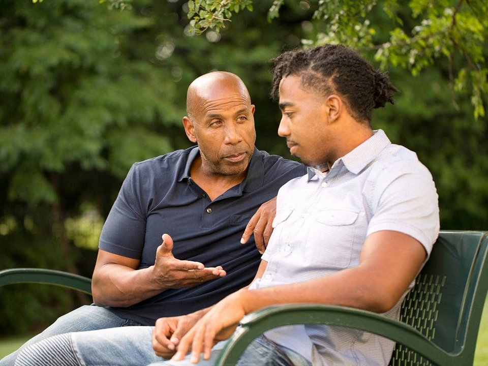 Father giving advice to son on bench in park