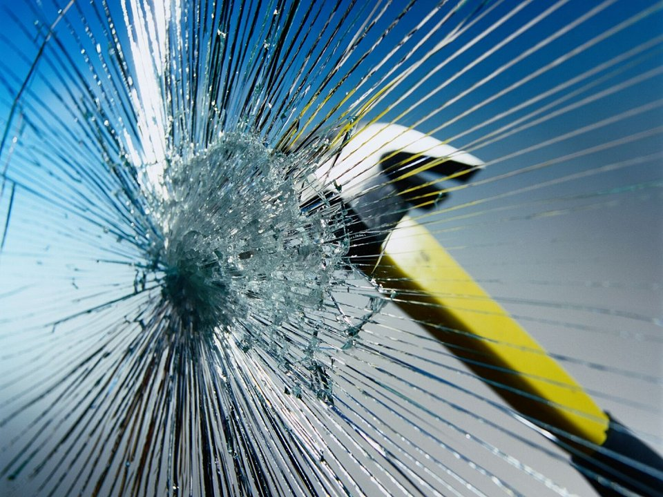 A hammer breaking glass