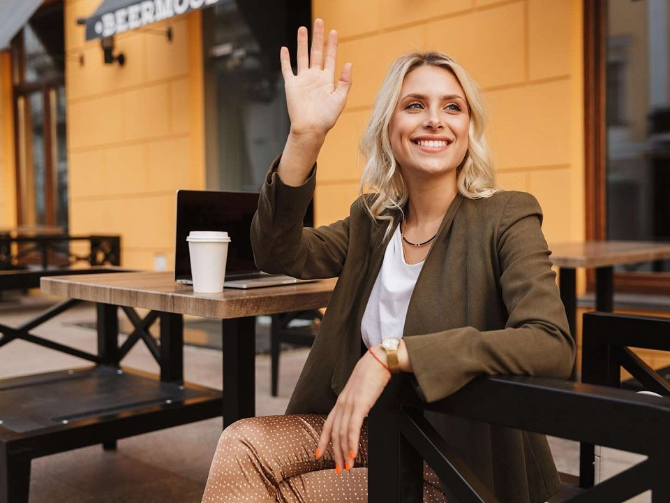 Woman sitting in a café waving hello to someone outside the frame
