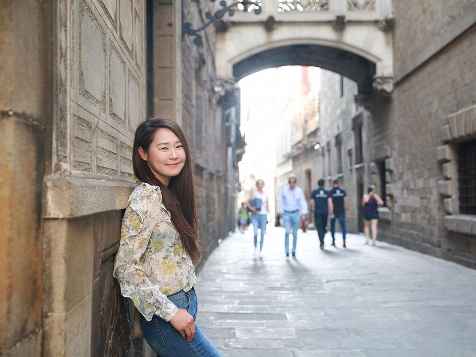 Student leaning against wall in front of the arch on Carrer del Bisbe in Barcelona