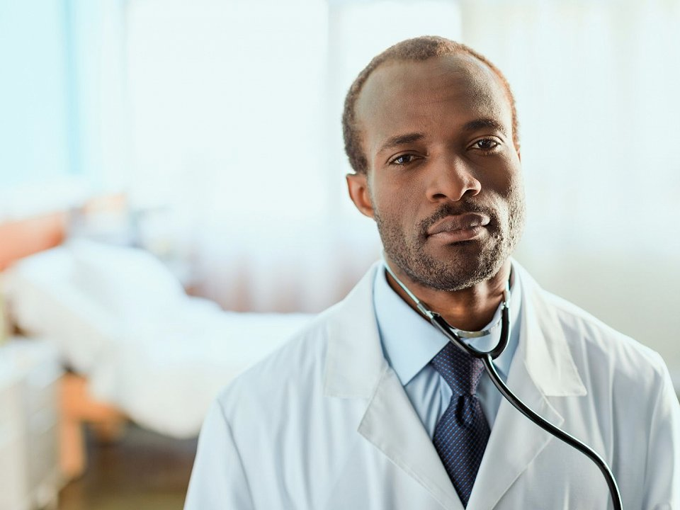 Doctor in lab coat standing in front of hospital bed.